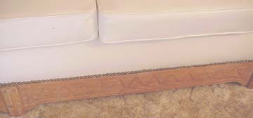 Picture of the carved detail on the left bottom of the couch as well as the nail head trim.