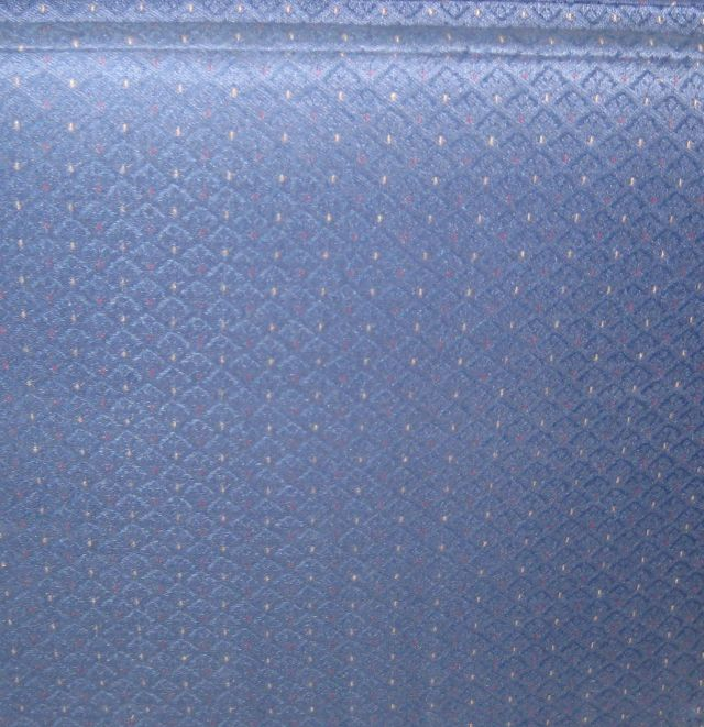 CLOSE UP OF FABRIC - DARK BLUE WITH TOUCHES OF DARK RED AND TAN